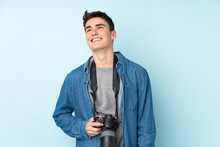 Teenager Photographer Man Isolated On Blue Background Laughing And Looking Up