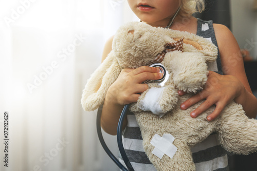 child playing doctor with soft toy. girl examining bunny with stethoscope at home