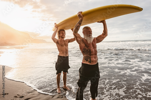 Happy friends with different age surfing together on tropical ocean - Sporty peo Wallpaper Mural