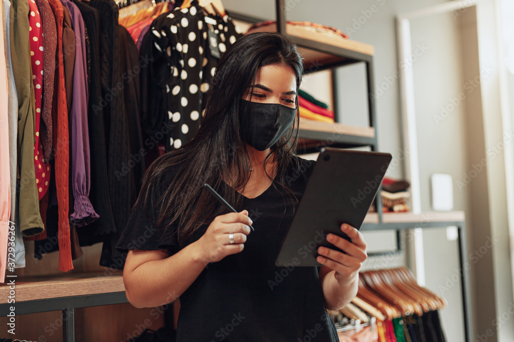 Fototapeta Latin woman owner of small business. Entrepreneurial woman working in her clothing store. Wearing face mask
