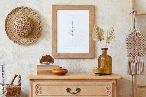 Photographie Stylish boho interior of living room with brown mock up poster frame, elegant accessories, flowers in vase, wooden shelf and hanging rattan hut