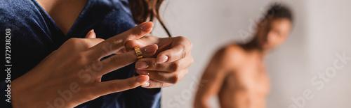 Photo Panoramic orientation of woman taking off wedding ring with shirtless man at bac