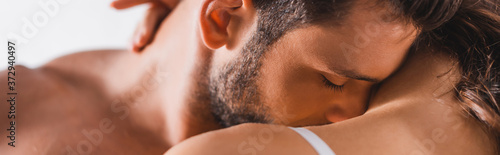 Fotografia Horizontal crop of shirtless man kissing shoulder of girlfriend on grey backgrou