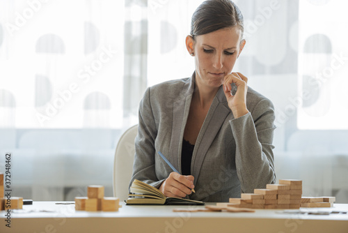 Frowning young businesswoman making notes in her notepad Canvas Print
