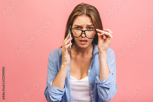 Fotografiet Oh no! Really? Shocked young woman using mobile phone, wearing casual, isolated on pink background