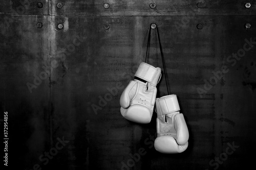 Fotografia White leather boxing gloves hanging on black wall