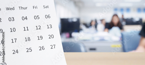 Foto White paper desk calendar on wood table top with blurred office interior backgro
