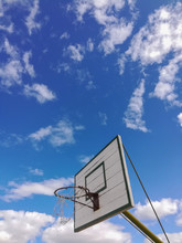 Vertical Low Angle Shot Of A Basketball Backboard Under The Cloudy Sky