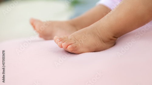 Infant baby legs on pastel pink background, newborn barefeet in a selective focu Wallpaper Mural