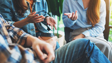 A Group Of Young People Sitting And Talking Together