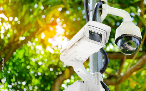 Fotografija Modern public CCTV camera on a electric pole with blurred natural background