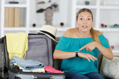 Photo woman packing suitcase pointing in shock at her wristwatch