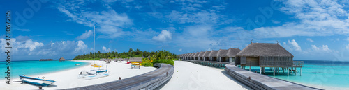 Panorama landscape of the tropical beach with over water bungalows and alms tree Poster Mural XXL