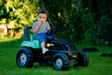 Baby Girl Playing With Toy Tractor In A Garden.