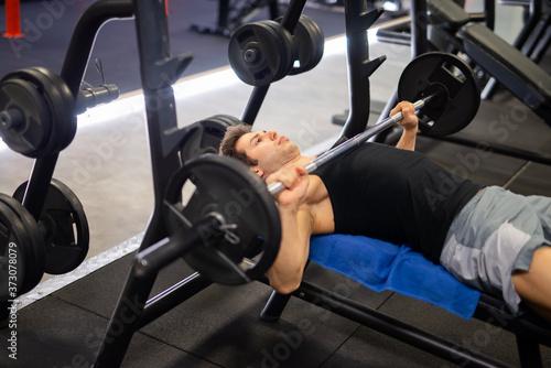 Obraz na płótnie Bodybuilder lifting a weight on the flat bench