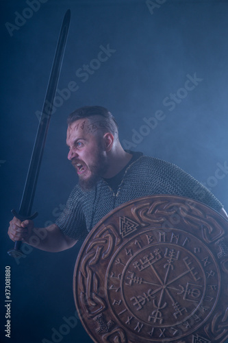 Studio photography: a half-length portrait of a Viking in chain mail, with a sword and shield in the smoke Fototapeta