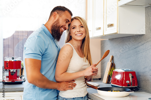 Young loving couple cooking together in kitchen Fototapeta