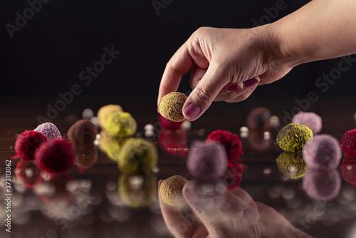 Fototapeta Closeup shot of a hand choosing a gourmet chocolate ball from an assortment of f