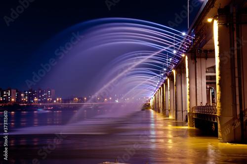 Fotografie, Obraz Amazing fantastic colorful fountain with blight at the bridge,