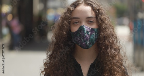 Young woman in city face portrait wearing a mask Fototapet