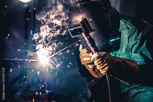 Fototapeta Metal welding steel works using electric arc welding machine to weld steel at factory