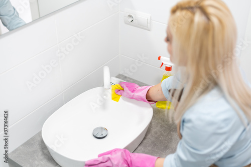 Fototapeta Housework and domestic lifestyle: woman doing chores in bathroom at home, cleani