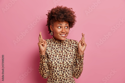 Cuadros en Lienzo Smiling hopeful fashionable woman with curly hair dressed in leopard jumper hold
