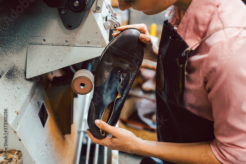 Fototapeta Woman cobbler working on machine in her shoemaker workshop
