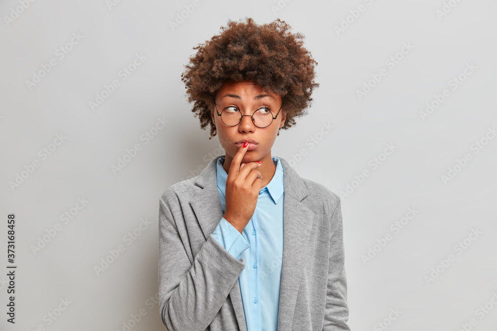 Fototapeta Serious sad female teacher in blue shirt and grey jacket, thinks over distance teaching, looks pensively aside. Businesswoman ponders on important business decision, makes assumption, touches lips