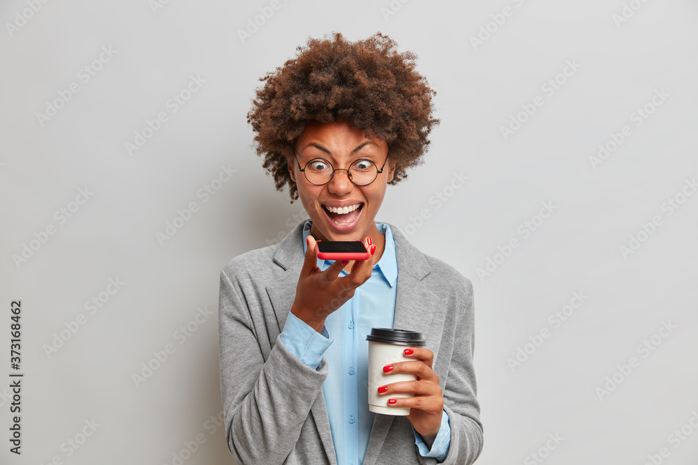 Fototapeta Angry female boss in grey formal outfit, has voice call, shouts angrily on coworker who made failure in business report, drinks takeaway coffee, spends time in office, solves financial problems