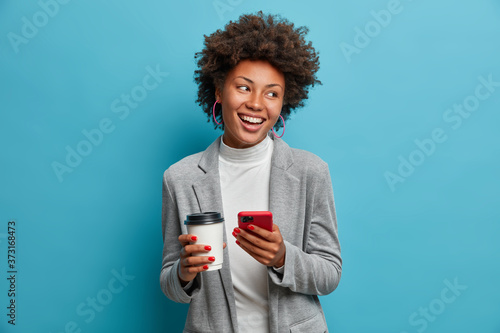 Canvas Print Successful Afro American entrepreneur in formal wear holds mobile phone, orders