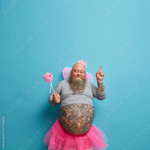 Obraz People, holiday, fun concept. Joyful obese man wears princess outfit, poses with magic wand, moves actively, has big tattooed stomach stands closed eyes points above on copy space blue background - fototapety do salonu