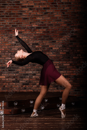 Beautiful young female classical ballet dancer on pointe shoes wearing a black l Fototapeta