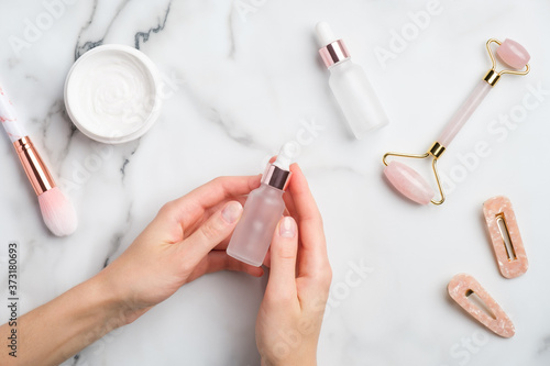 Obraz na plátně Female hand holding serum bottle over marble table with moisturizer cream, makeup brush, face massage roller