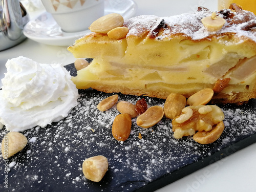 Fotografia Closeup shot of an apple pie with nuts and cream