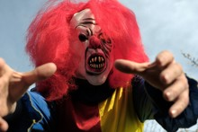 Halloween Holiday. Scary Aggressive Clown With Red Hair  On  Blue Sky Background. Creepy Clown Costume. Festival And Carnival Concept. Horror And Fear.
