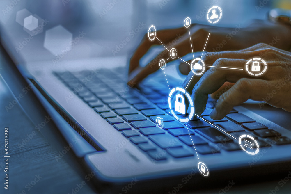 Fototapeta Business, technology, internet and networking concept. Young businesswoman working on his laptop in the office, select the icon security on the virtual display.Blue tone concept