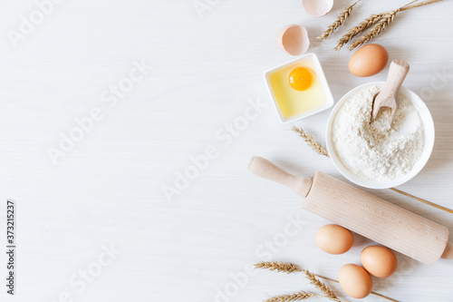 Ingredients and tools for dough preparation on white wooden background top view.