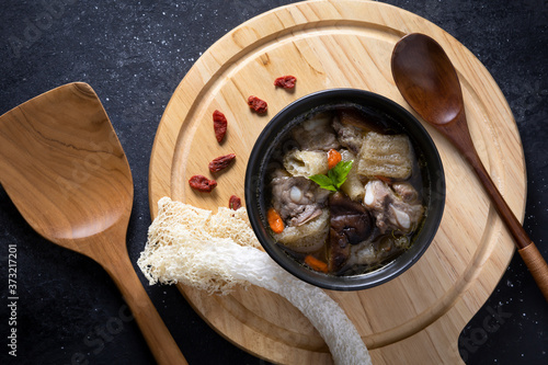 Cuadros en Lienzo Stewed bamboo pulp soup with Chinese medicine on a wooden floor.