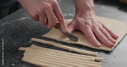 man cutting flat dough with knife Billede på lærred