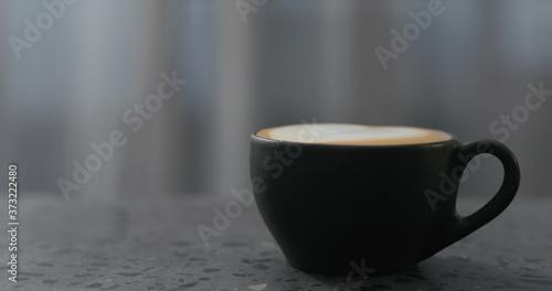 Fotografie, Obraz cappuccino in black cup on terrazzo countertop