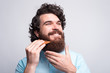 canvas print picture - Photo of happy man with beard using wooden hipster comb over white background.