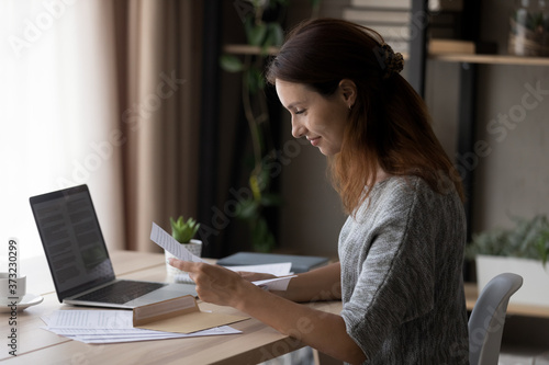 Smiling young Caucasian woman sit at table at home open envelope read paper corr Fotobehang