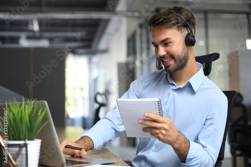 Fotografia Smiling male business consultant with headphones sitting at modern office, video call looking at laptop screen