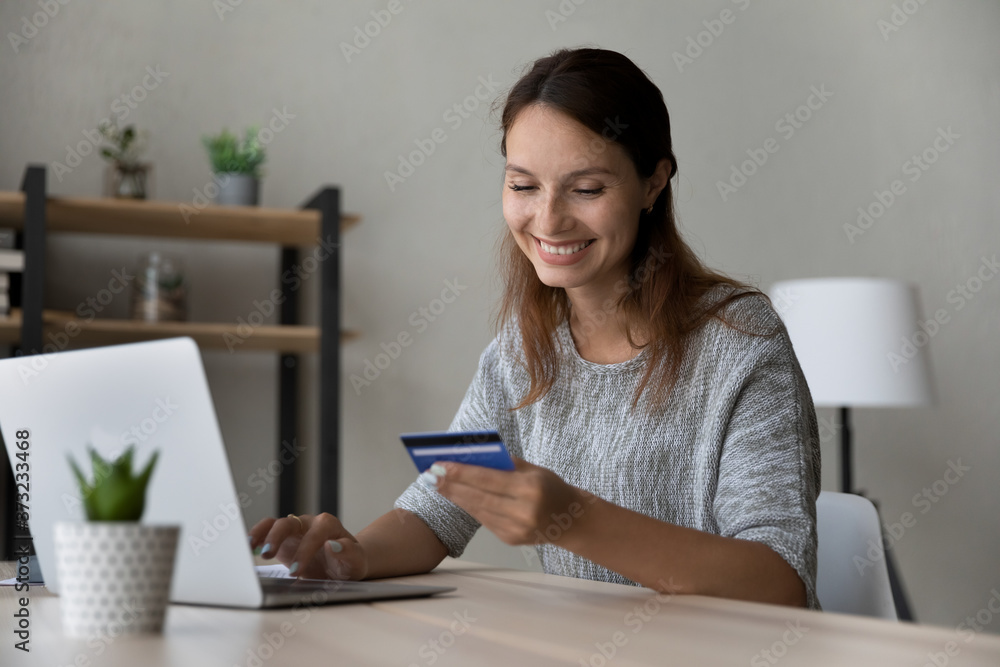 Fototapeta Smiling millennial Caucasian female sit at table at home make online payment purchase using credit card, happy young woman shopping on internet, pay on web with secure banking service system on laptop