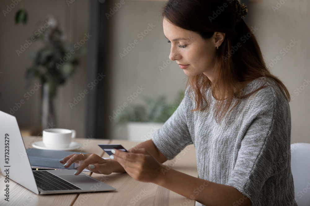 Fototapeta Young Caucasian woman sit at table make online payment or purchase using secure web banking system on computer, millennial female shopping on internet, pay bills with credit card on laptop on web