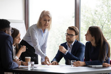 Aged Woman Experienced Employee Drawing Attention Of Young Colleagues To Paper Documents On Office Meeting, Mature Female Trainer Or Leader Pointing Diverse Staff To Important Detail In Business Plan
