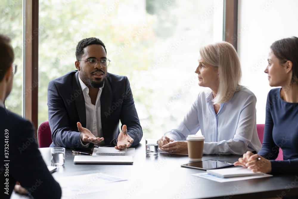 Fototapeta Confident african trainer or coach giving recomendations to diverse group of clients, dark-skinned boss holding a meeting with staff, multiethnic team listening to leader explaining his point of view
