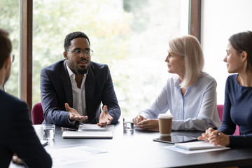 Confident african trainer or coach giving recomendations to diverse group of clients, dark-skinned boss holding a meeting with staff, multiethnic team listening to leader explaining his point of view