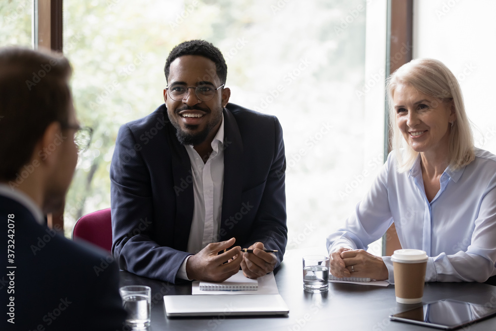 Fototapeta Inspired african businessman talking about benefits of his startup on meeting with potential investors, excited black agent and his mature female colleague convincing client in profit of their product